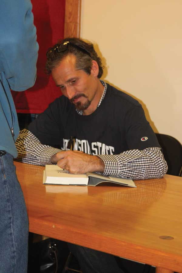 Charlie LeDuff signs a copy of his book