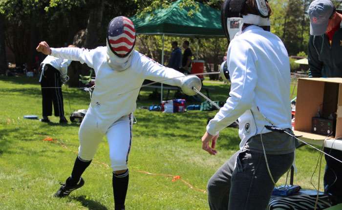 Two fencers cross swords during a bout