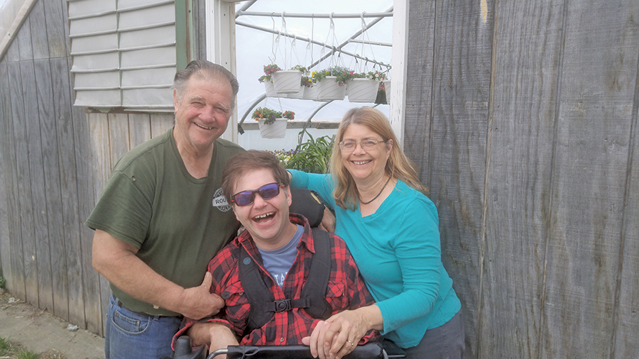 Joe, Jay and Anne Tisbert pose in front of one of their greehouses