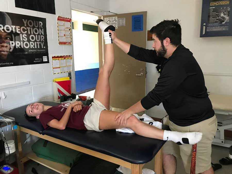 Ben Michon in the athletic trainer's office with student athlete Morgan Grace