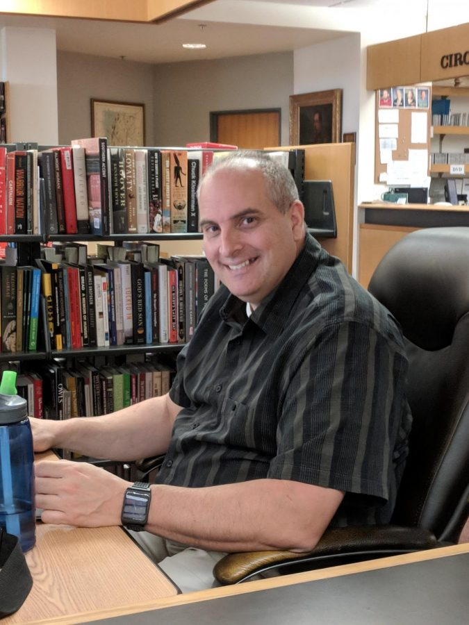 Michael Dente sits at his office chair in Willey Library in early September 2018