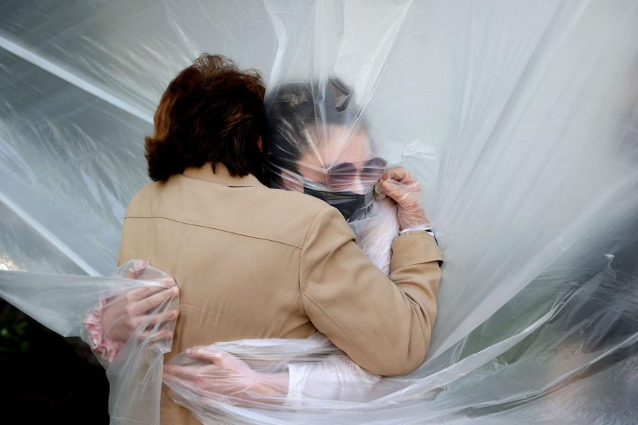 Two people embrace in the only way two people can during a pandemic: through a plastic sheet and wearing face masks.
