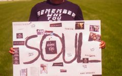 Devyn Thompson standing with her sign to represent her recently published book of poetry.